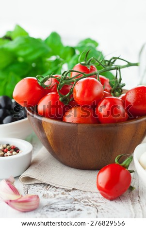 Ripe fresh cherry tomatoes on rustic white wooden background, mediterranean cuisine, selective focus - stock photo