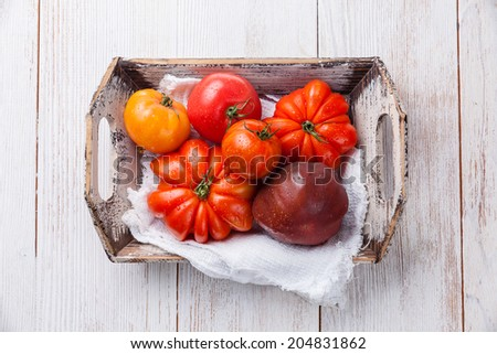 Ripe fresh colorful tomatoes in wooden box on white wooden background - stock photo