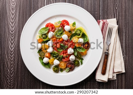 Ripe fresh colorful tomatoes salad with basil and mozarella mini on gray wooden background  - stock photo