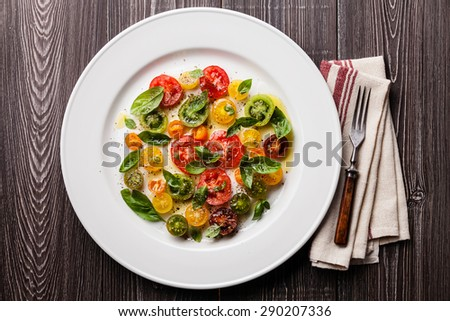 Ripe fresh colorful tomatoes salad with basil and olive oil on gray wooden background  - stock photo