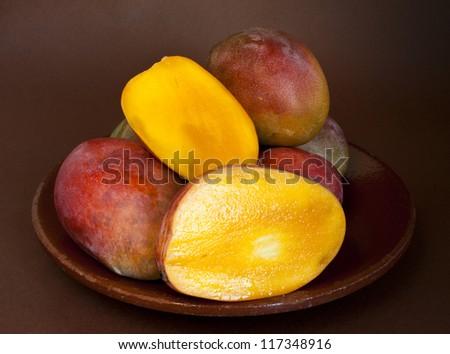 Ripe fresh mango on old ceramic plate - stock photo