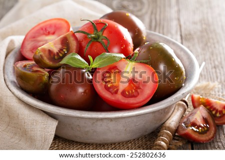 Ripe fresh tomatoes cut and whole in a bowl - stock photo