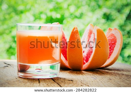Ripe grapefruit with juice on table close-up. - stock photo