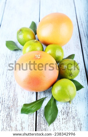Ripe grapefruits and limes on wooden background - stock photo