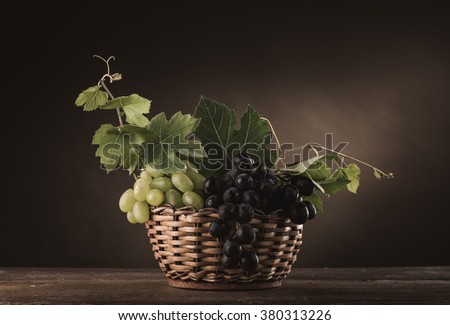 Ripe grapes in a basket on a rustic wooden table with vine leaves, classic still life - stock photo