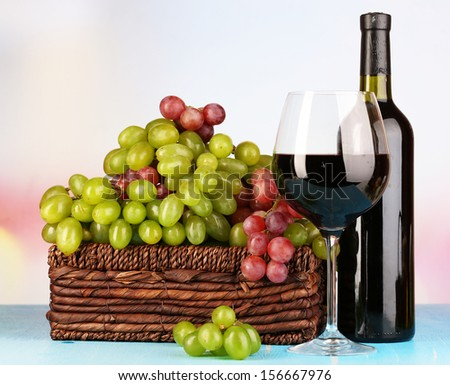 Ripe green and purple grapes in basket with wine on wooden table on bright background - stock photo