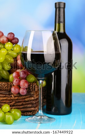 Ripe green and purple grapes in basket with wine on wooden table on natural background - stock photo
