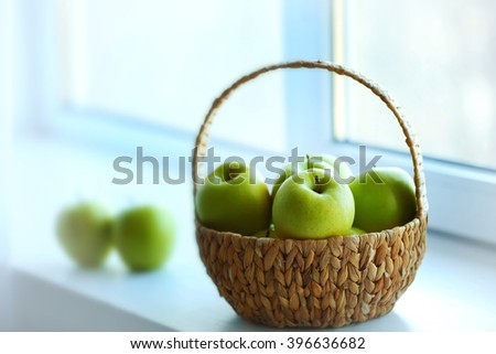 Ripe green apples in basket on a windowsill - stock photo
