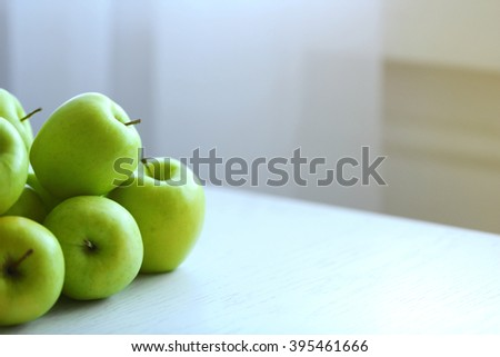 Ripe green apples on a kitchen table - stock photo