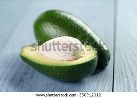ripe green avocado on blue wood table, close up photo - stock photo