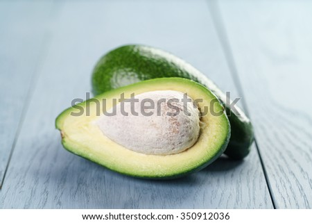 ripe green avocado on blue wood table, close up photo