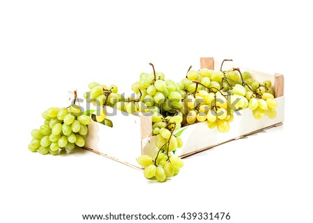 Ripe green grapes in a wooden crate box isolated