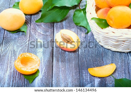 ripe juicy apricots in a basket on a wooden background - stock photo
