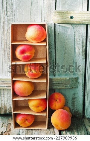 ripe juicy apricots in a cardboard box on a wooden background.health and diet food - stock photo