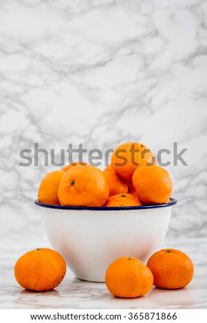 Ripe juicy mandarin fruit in enamel bowl on white marble - stock photo