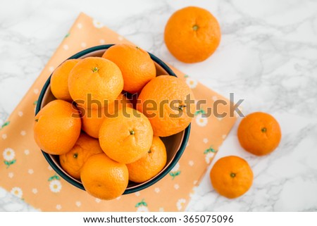 Ripe juicy mandarin tangerine citrus fruit in enamel bowl on white marble - stock photo