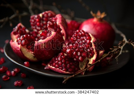 Ripe juicy red pomegranate with a drop of juice. Macro - stock photo