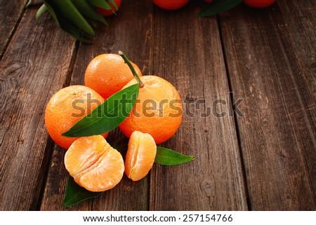 Ripe juicy tangerine, orange mandarin with leaves on wooden table - stock photo