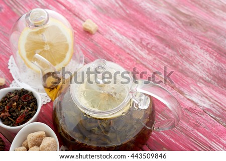 Ripe lemon, cinnamon and fruit drink in glass teapot on wooden background