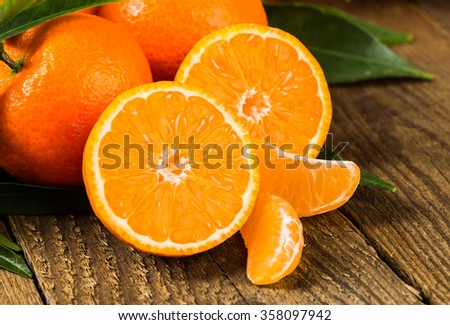 Ripe Mandarin fruit peeled open and place on old rustic look timber with group of mandarin fruits and leaves out of focus on the background