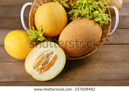 Ripe melons with green leaves in basket on table close up - stock photo