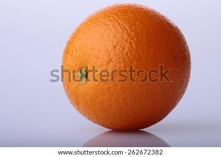Ripe orange fruit on blue background with reflection - stock photo