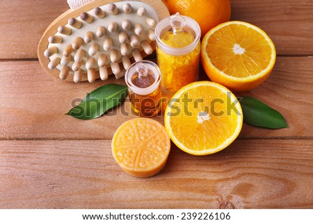 Ripe orange with bottles of bath salt and essential oil, bar of soap and wooden brush on wooden background - stock photo