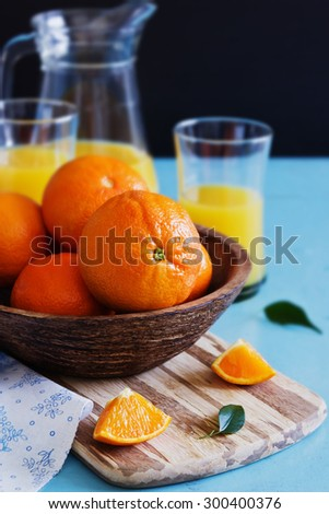 ripe oranges in a wooden bowl and orange juice on a blue wooden background.health and diet concept. selective focus - stock photo