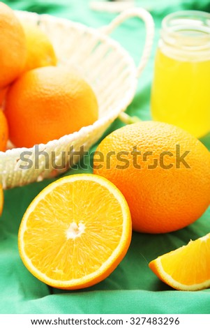 Ripe oranges in basket on green background