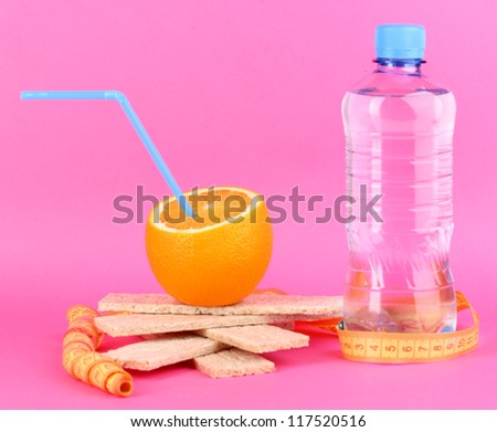 Ripe oranges, loafs and bottle of water as symbol of diet on pink background - stock photo
