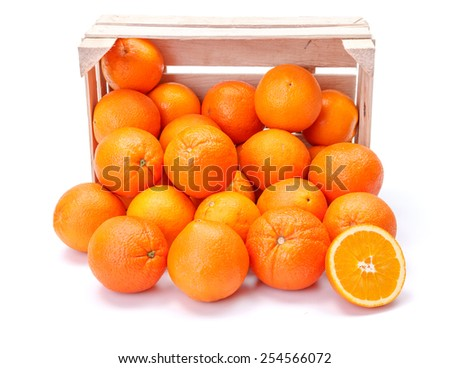 Ripe oranges spilling out of wooden crate. Citrus sinensis - stock photo