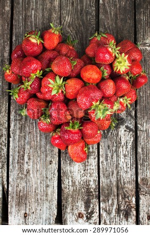 Ripe organic strawberries on rustic wood background in shape of heart - stock photo