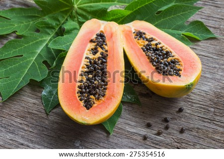 Ripe papaya with green leaf on wooden background. - stock photo