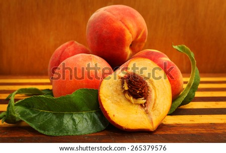 ripe peach with leaf isolated on wood background - stock photo