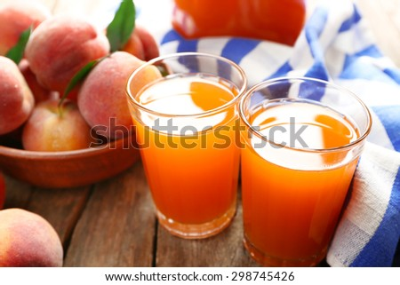 Ripe peaches and juice in glass on wooden background - stock photo