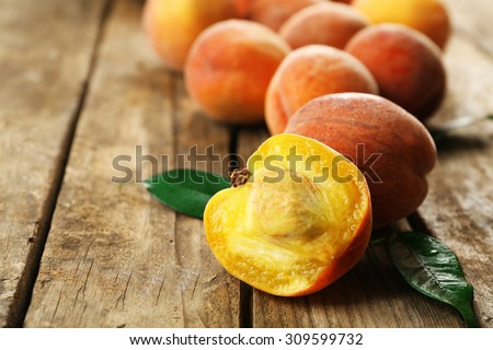 Ripe peaches on wooden background - stock photo