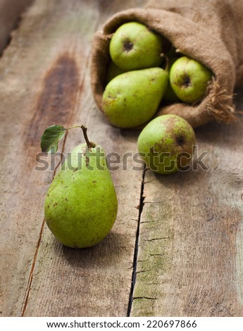 Ripe pear on a wooden background vertical - stock photo
