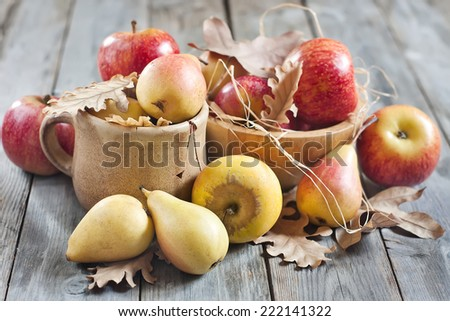 Ripe pears and apples with dry fall leaves on wooden background. Selective focus. - stock photo