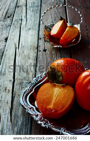 Ripe persimmon and cut persimmon on rustic wooden background. - stock photo