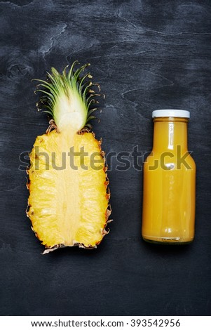 ripe pineapple and bottle of juice over black background. top view - stock photo