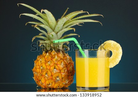 Ripe pineapple and juice glass on dark blue background - stock photo