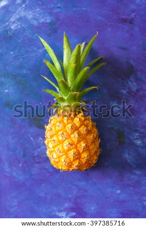 ripe pineapple on a blue background, tropical theme - stock photo