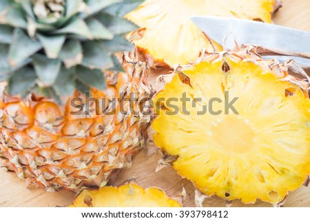 Ripe pineapple slices on wooden cutting board - stock photo