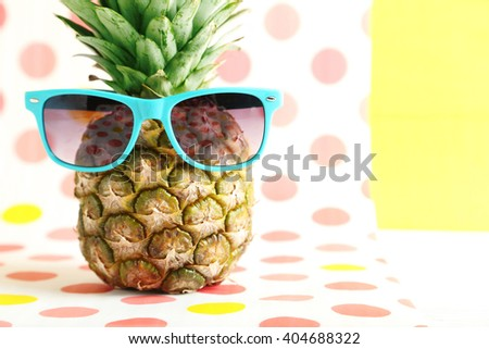 Ripe pineapple with sunglasses on a colorful background - stock photo