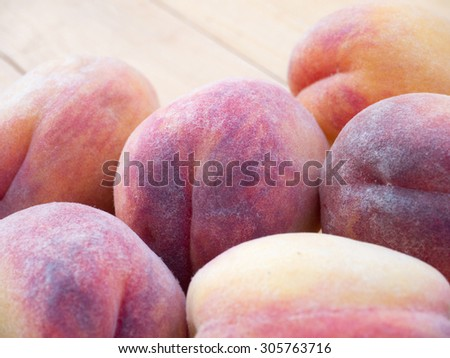 Ripe pink and yellow peaches on the rustic wooden table