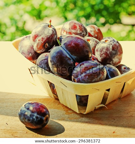 Ripe plums in wooden box on wooden table on natural background - stock photo