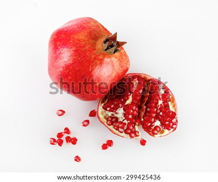 Ripe pomegranate and its half with reflection on a light background. Studio shot. Top view. - stock photo