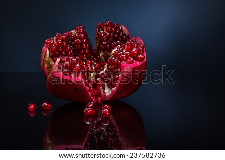 ripe pomegranate fruit on blue background - stock photo