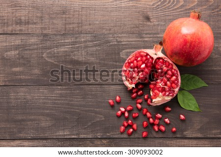 Ripe pomegranate fruit on wooden vintage background. - stock photo