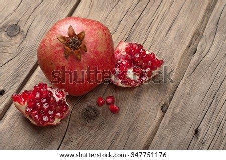 Ripe pomegranate fruit with slices of pomegranate on a wooden table closeup. View from above. Copy space - stock photo